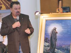 "Thomas Kinkade unveils his painting ""Prayer For Peace"" at the opening of the exhibit ""From Abraham to Jesus"" on Sept. 15, 2006, in Atlanta."