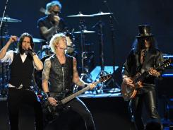 Guns N' Roses' Duff McKagan, center and Slash, right, perform with guest vocalist Myles Kennedy, left, after induction Saturday into the Rock and Roll Hall of Fame in Cleveland.