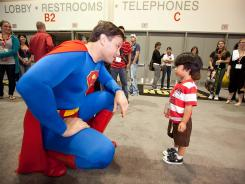 "A young fan meets an attendee dressed as Superman in a scene from Morgan Spurlock's ""Comic-Con Episode iV: A Fan's Hope."""