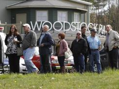 People wait outside the Woodstock Playhouse to board buses to go to a wake for musician Levon Helm at his home in Woodstock, N.Y., on Thursday, April 26, 2012.