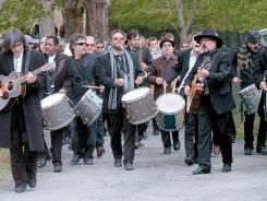 A band leads mourners out of Woodstock Cemetery in Woodstock, N.Y., after Levon Helm was brought there for burial Friday.