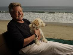 Ryan O'Neal, with his dog Mozart, enjoys the surf and sand in Malibu, Calif. where Farrah Fawcett photographed the sunset every evening. O'Neal writes about their story in 'Both of Us.'