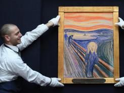 Gallery technicians at Sotheby's adjust 'The Scream' by Edvard Munch ahead of its auction Wednesday.