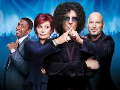 Howard Stern, foreground, replaces Piers Morgan as a judge on 'America's Got Talent.' Host Nick Cannon, left, and judges Sharon Osbourne and Howie Mandel don't seem to miss Morgan.