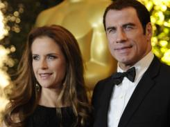 Sued: John Travolta (with wife Kelly Preston) wasn't even in same city as his accusers at the time, his lawyer says.