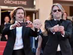 Brad Pitt and Killing Them Softly director Andrew Dominik take some photos of their own at the film's premiere in Cannes.
