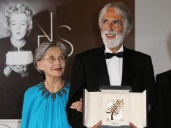 "Michael Haneke, right, poses for photographers with the Palme d'Or award for ""Amour"" alongside Emmanuelle Riva at the 65th international film festival in Cannes on Sunday."