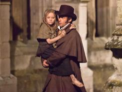 On the road to redemption: French ex-convict Jean Valjean (Hugh Jackman) takes in young Cosette (Isabelle Allen) in 'Les Miserables.'