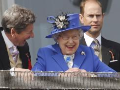 Queen Elizabeth II looks out from the balcony during the Epsom Derby, the start of a four-day Diamond Jubilee marking her 60th year on the throne.