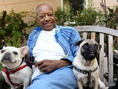 Bobby Womack sits with dogs Music, left, and Wo. With health and drug problems behind him, Womack returns with 'The Bravest Man in the Universe.'