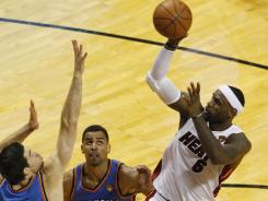 He shoots and scores (in the Nielsens): The Miami Heat's LeBron James, right, fires off a shot during Game 3 of the NBA Finals. The first three games of the series occupied the top three shows in the ratings.