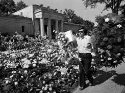 In this Aug. 18, 1977, file photo, a florist adds more arrangements at the mausoleum where singer Elvis Presley was to be entombed in Memphis, Tenn.