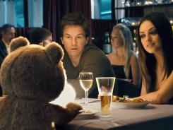 Ted (voiced by Seth MacFarlane) and his best friend, John (Mark Wahlberg), have a third wheel: John's girlfriend, Lori (Mila Kunis).