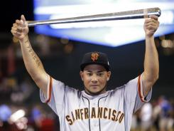 Melky Cabrera, of the San Francisco Giants, shows off his MVP trophy after the National League won the MLB All-Star Game 8-0. The game drew 10.9 million viewers on Fox.
