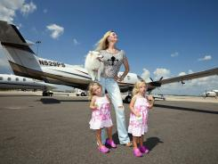 Before the fall: Jackie Siegel, the titular star of 'Queen of Versailles,' with her twin girls, Jordan and Jacqueline, in front of their private plane in Orlando.