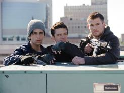 Josh Peck, left, Josh Hutcherson, and Chris Hemsworth do battle with invading North Korean forces in 'Red Dawn.'