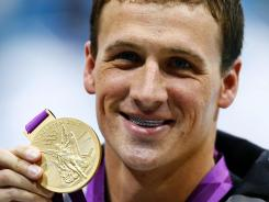 Ryan Lochte shows off his gold medal and American flag grill after winning the 400m IM finals.