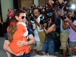 Camera shy: Suri Cruise, 6, clings to her dad, Tom Cruise, as they are snapped by a wall of photographers outside their New York hotel.