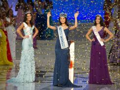 Miss World 2012 winner Yu Wenxia of China waves as she stands next to second place contestent Miss Wales Sophie Moulds, left, and third place Miss Australia Jessica Kahawaty, Aug. 18.