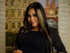 "Snooki from the cast of the MTV hit show ""Jersey Shore,"" pats her baby bump at Rivoli's Restaurant, on July 9, 2012."