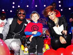 Singer and producer will.i.am along with featured vocalist Eva Simons appear with 6-year-old Los Angeles MDA Goodwill Ambassador Lucas Cook during the 'Show of Strength' taping at CBS Studios in Los Angeles.