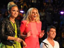 New 'X Factor' judges Demi Lovato, left, and Britney Spears take their places next to Simon Cowell and L.A. Reid Wednesday.