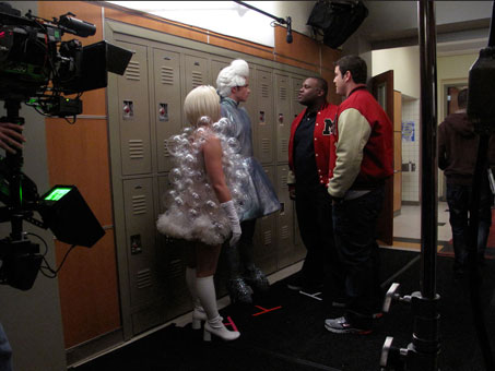 Tina and Kurt stand up to a couple of McKinley High jocks during rehearsal of a scene in the high school hallway.