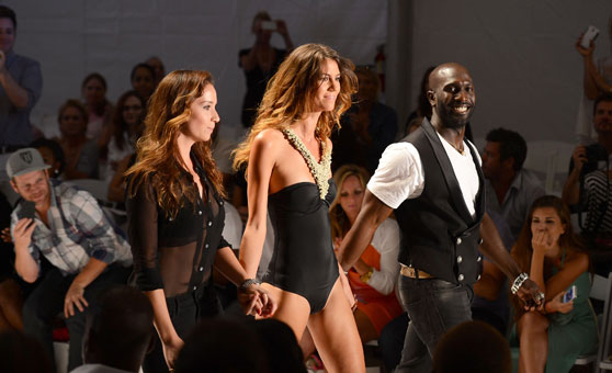 Designers and co-founders Stephanie Thais Fajardo, left, and Kevin Fitzpatrick walk the runway with their model at the Cote D' Or Swimwear show Monday.