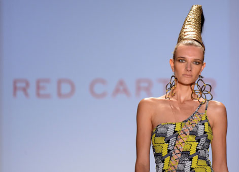 A model presents a one-shouldered Red Carter design and rocks a towering hairstyle. 