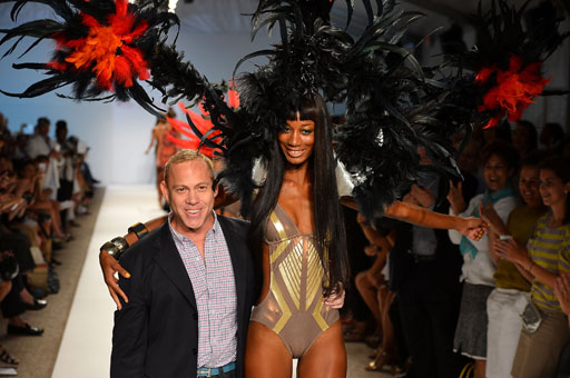 Designer Red Carter walks the runway with a model in his swimwear show Sunday.