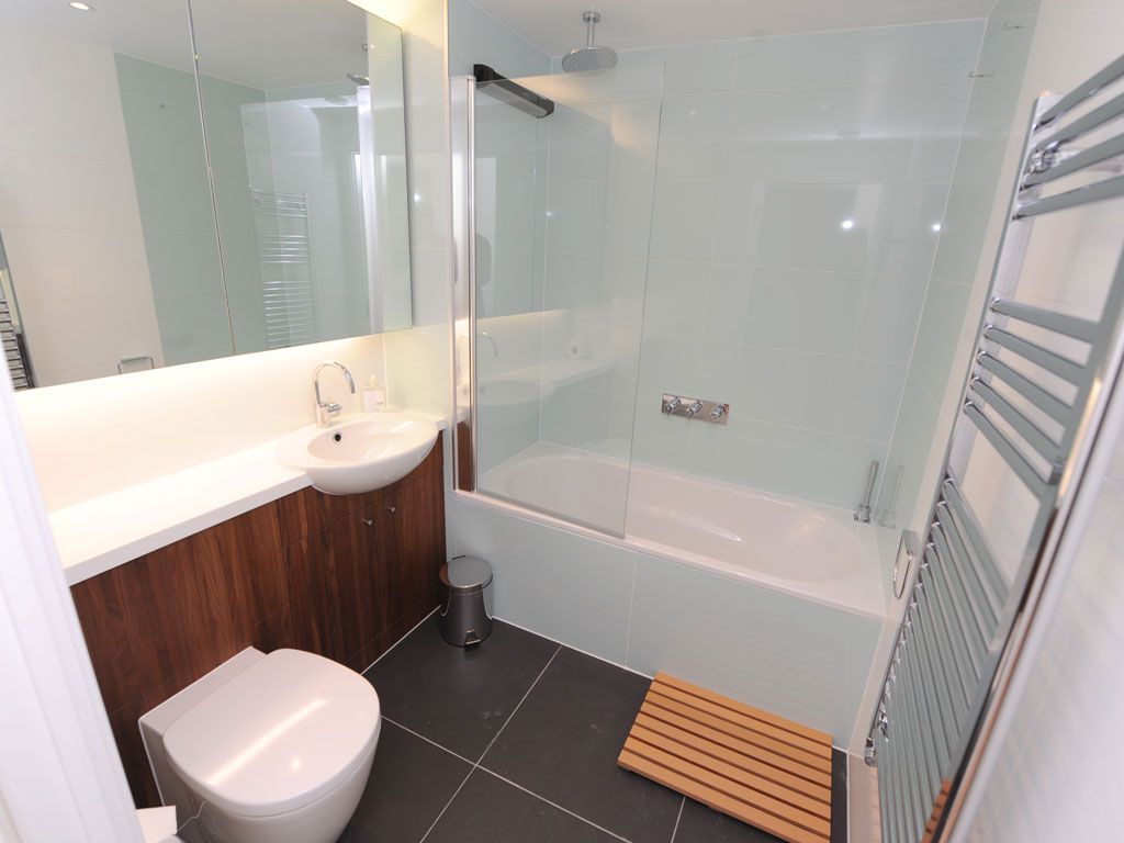 An apartment bathroom in London shows the push towards compact baths with clean lines, sleek finishes and limited upgrades such as the towel-warming rack (By Dominic Lipinski, AP).