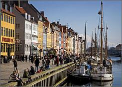 The area around the Nyhavn (Newharbour) in Copenhagen, Denmark, bustles with pedestrians.