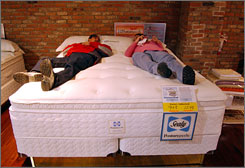 Joel and Elizabeth Perea try out a bed at American Furniture Warehouse in Englewood, Colo.