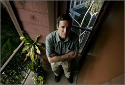 Andy Sobel stands on the balcony of his condominium in San Diego Thursday. He's six months behind on his payments.
