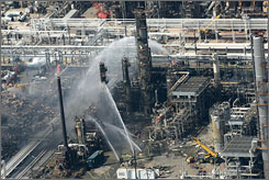 Firefighters pour water onto a smoldering unit after an explosion at the BP oil refinery in 2005 in Texas City.