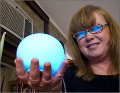 Jill Amoni has a glass orb from her utility company that glows in six colors, from blue to red, in response to wireless signals to reflect price changes in her utility rates throughout the day.