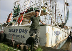Shrimp boat owner, Loi Le, 50, finishes up a day of grinding rust from his boat, Lucky Day. It was swept two miles inland during Katrina, and it took Loi three months and $150,000 to fix it.