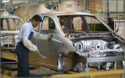A worker on the GM assembly line in Valencia, Venezuela, attaches parts to a Chevy Spark.