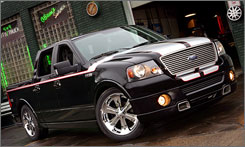 Huge wheels, a lowered stance and dramatic racing stripes mark the truck styled by Chip Foose.