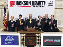 Michael Lister, center, CEO of Jackson Hewitt Tax Service, kicks off the 2007 tax season by ringing the closing bell at the New York Stock Exchange in January.