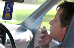 Irvin Rosenfeld smokes marijuana in his car during a work break. He uses medical marijuana to relieve pain caused by benign bone tumors.