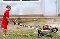 A 9-year-old in Kingfisher, Okla., unclogs his mower of wet grass clippings.