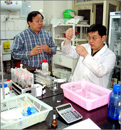 Dr. Wu Yongning (left), national co-coordinator for food safety research in China, and research assistant Zhang Lei test for arsenic in seaweed at the laboratories of the Office for Monitoring &amp; Control of Chemical Contaminants in Beijing. 