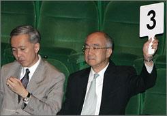 A representative of Sino Land raises a bid beside company Chairman Robert Ng, left, during a land auction in Hong Kong on May 8.