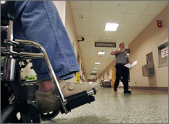 A man waits in a wheelchair in the emergency room of West Jefferson Medical Center on April 30 in Marrero, La.