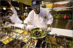 John Anderson mixes a salad at a Whole Foods Market in New York. Majory Louis is at left.