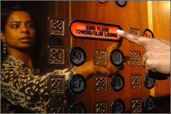 Rubie Lloyd of the Chicago Sheraton is reflected in the elevator as she pushes a button for the Club Lounge.