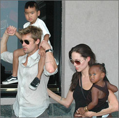 Adoption advocates and movie stars Brad Pitt and Angelina Jolie with their kids on a trip to India. Across the USA, employers are increasingly offering help to workers who want to adopt.