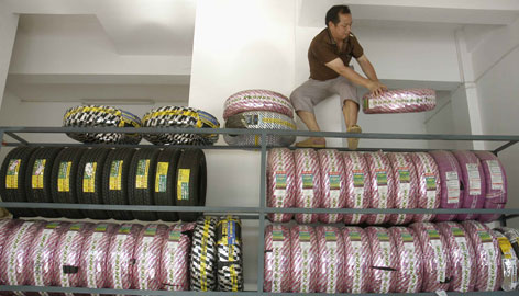 A vendor piles up tires at a store in Baokang, Hubei Province, China. About 450,000 Chinese-made tires are under recall in the USA.