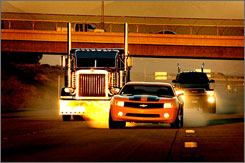 Autobots (the good guys) drive down the road in Transformers. GM has high hopes for its vehicles in the summer blockbuster.